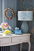 A table lamp with a patterned shade and flowers on a country house style wall table