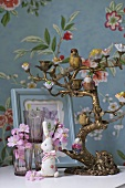 A candelabra, animal figurines and glasses against a wall with floral patterned wallpaper