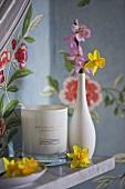 Flowers in white vase on shelf