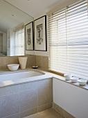 Cream bathroom with stone ledges and surround on bath tub