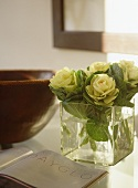 Close up of flowers in glass cube vase next to ceramic bowl and open book on glass top side table.