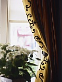 A detail of a window with gold curtains held back