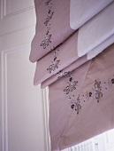 A detail of a neutral embroidered roman blind
