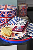 Fairy cakes on a plate next to a Union Jack tin