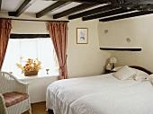 Bett und Korbsessel unter Holzbalkendecke im Landhausstil