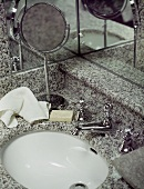 Granite wash hand basin, mirrored walls and a shaving mirror with hand towel and soap.