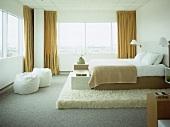 Doppelbett auf Podest mit Flokati belegt und Fensterfront mit gelbem Vorhang