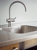 A detail of a modern kitchen, a stainless steel sink and work top, chrome tap,