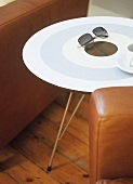 A detail of a modern sitting room, a round painted table, set between leather armchairs, wooden floor,