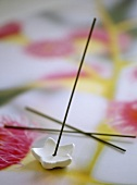 Incense sticks and star shaped holder on floral patterned tablecloth.