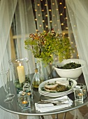 Metal table, draped with white sheer curtain, set for meal in gazebo.