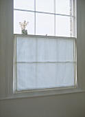 A detail of a simple sash window with a neutral blind curtain