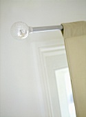 A detail of light fabric curtains hung upon a metal curtain rod with a silver ball finial