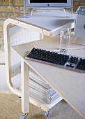 A detail of a modern home office showing a desk, computer screen, keyboard, portable trolley storage unit on wheels