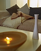 Vase and burning candle on a table in front of a couch with cushions