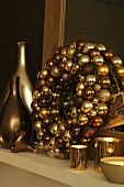 Wreath made of golden Christmas ball ornaments with tea light and vases in shiny metallic colors