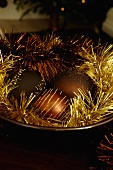Christmas ball ornaments with gold tinsel in a bowl