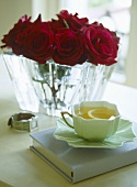 A detail of a cup of lemon tea resting on a book, red roses in a glass vase