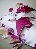 A detail of a girlÕs bedroom, single bed with pink floral cover, retro style radio, slippers,