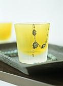 Kette auf gelbes Glas drapiert