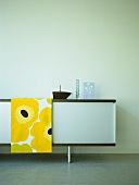 A detail of a modern, sitting room, retro styled sideboard cabinet, bright yellow and black cloth, glassware,