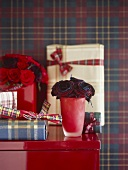 A detail of a red vase with roses, wrapped presents, set on a red cabinet,