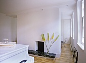 A modern, white minimal room, piano, modern fireplace, marble step, central wall as partition to next room,
