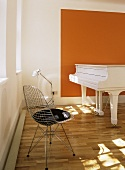 A modern white and orange minimalist music room, grand piano, metal lattice chair, wooden floor, lamp,