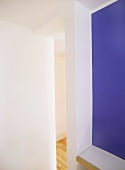 An abstract detail of white and purple walls and a view through a narrow opening into a hallway