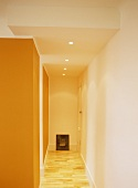 A detail of a modern hallway, painted orange wall, wooden floor,
