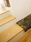 A detail of wooden steps, white walls, books on shelf, marble step,