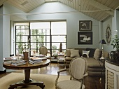 A country style, traditional sitting room, panelled slanted roof, fireplace, beige sofa and chairs, round polished table,