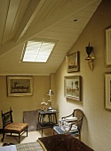 A detail of a country style bedroom, wood panelled sloping ceiling, bed, chairs, side table, skylight,