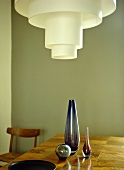 Three purple glass vases on wooden table with retro ceiling light above