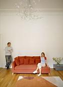 Frau auf roter Chaiselongue und Mann an Wand lehnend