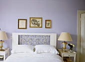 A detail of a traditional, pale blue bedroom with double bed, decorative headboard, side tables, lamps