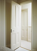 A view through an open, painted panelled interior door into a neutral hallway