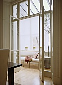 View through open French doors to a modern conservatory sitting room, upholstered sofa, wood floor