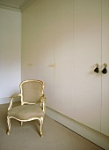 A detail of a bedroom, with a Louis XV style armchair and modern fitted wardrobes