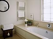 A detail of a modern, neutral en suite bathroom showing bath, chrome towel rail radiator, chest