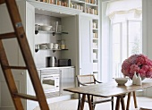A modern, compact kitchen built in and concealed behind cupboard doors, wood dining table, chairs