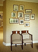Display of black and white pictures above pair of old cinema seats