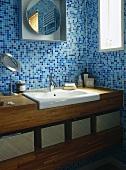 Washbasin set in wooden unit in blue tiled bathroom