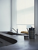 A detail of a modern, kitchen, granite work top with sink beneath window, ceramic coffee pot,