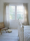 White room with Victorian frame bed and wooden chair and ostrich eggs in window.