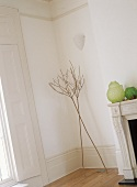 Corner of white room with ornamental twigs and shutters on window.