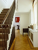 A traditional neutral hallway with parquet wood floor, staircase with view through open door beyond