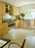 A modern, neutral kitchen with dining area, tiled floor, wood units, stainless steel sink unit, range oven