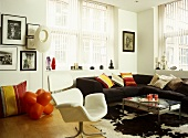 Eclectic sitting room with a wood floor, black sectional sofa, modern armchair, colourful cushions, and an animal skin rug.