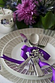 A place setting with cutlery and a purple ribbon in front of a bunch of flowers